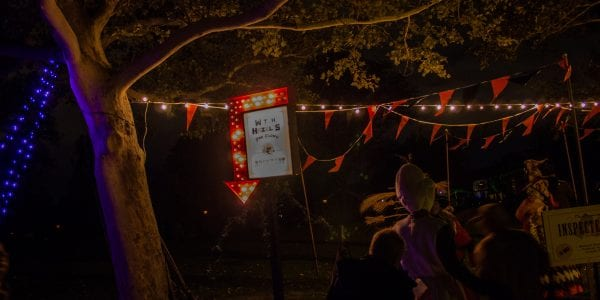night time scene with string lights and a red arrow with a sign attached to it.