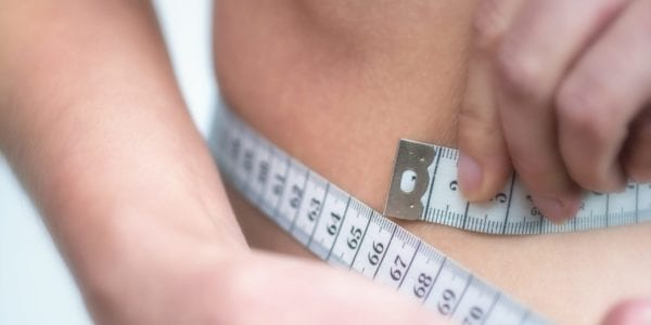 Person measuring their waist