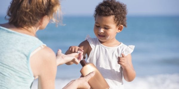 mom putting sunscreen on child at beach