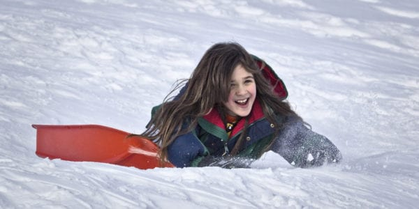 Little girl smiling while she sleds down a snow hill