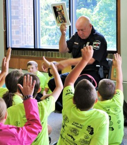 Walker Police Department Officer Gil Redzinski quizzes kids at a recent Life EMS Ambulance Camp 911 event about strangers.