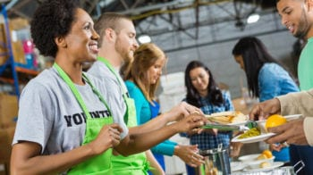 Volunteers serving healthy hot meal at a soup kitchen.