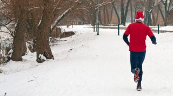 Man running in a Santa hat through snow.