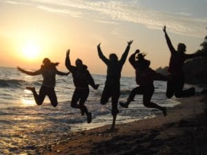 the group jumping on a beach with a sunset in the background