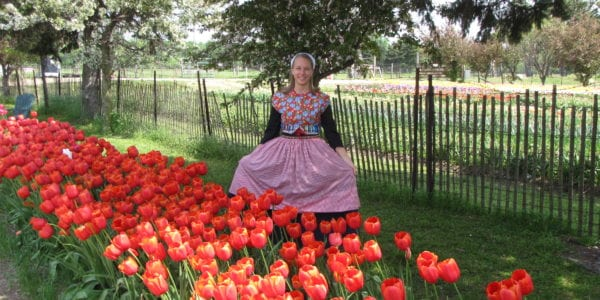 Nicole Prins in front of Tulips in a Dutch outfit