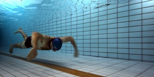 A swimmer underwater in a pool