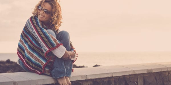 smiling woman cuddled up in a blanket sitting on a bench/ledge overlooking water