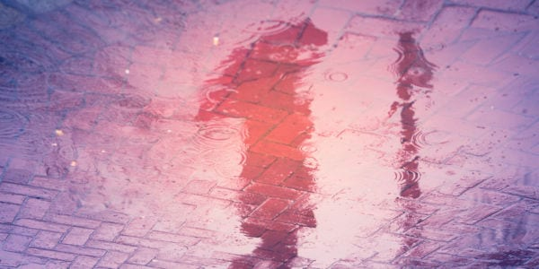 Image of woman holding an umbrella reflected in a puddle.