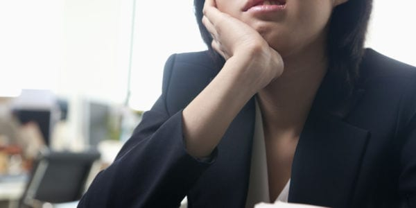 Image of a young woman bored at her desk