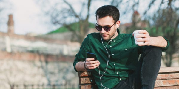 Young man drinking coffee listening to music on his smartphone through earbuds.