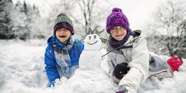 Kids making a snowman in the snow.
