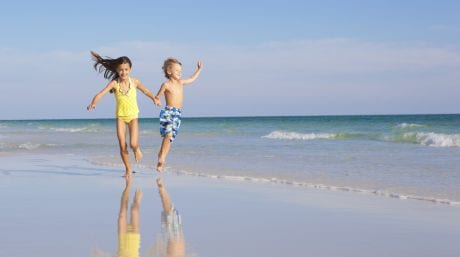 Two children running along the shoreline.