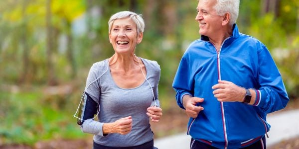 Smiling senior couple jogging in the park