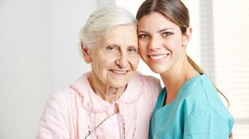 Smiling female caregiver embracing happy senior woman in nursing home