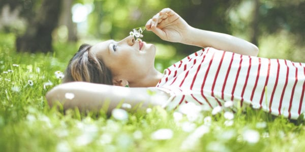 Woman relaxing in grass smelling a flower
