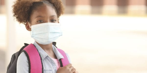 Little girl going to school with a mask on