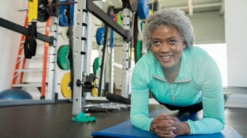 Senior woman smiling while doing a planking exercise in modern gym