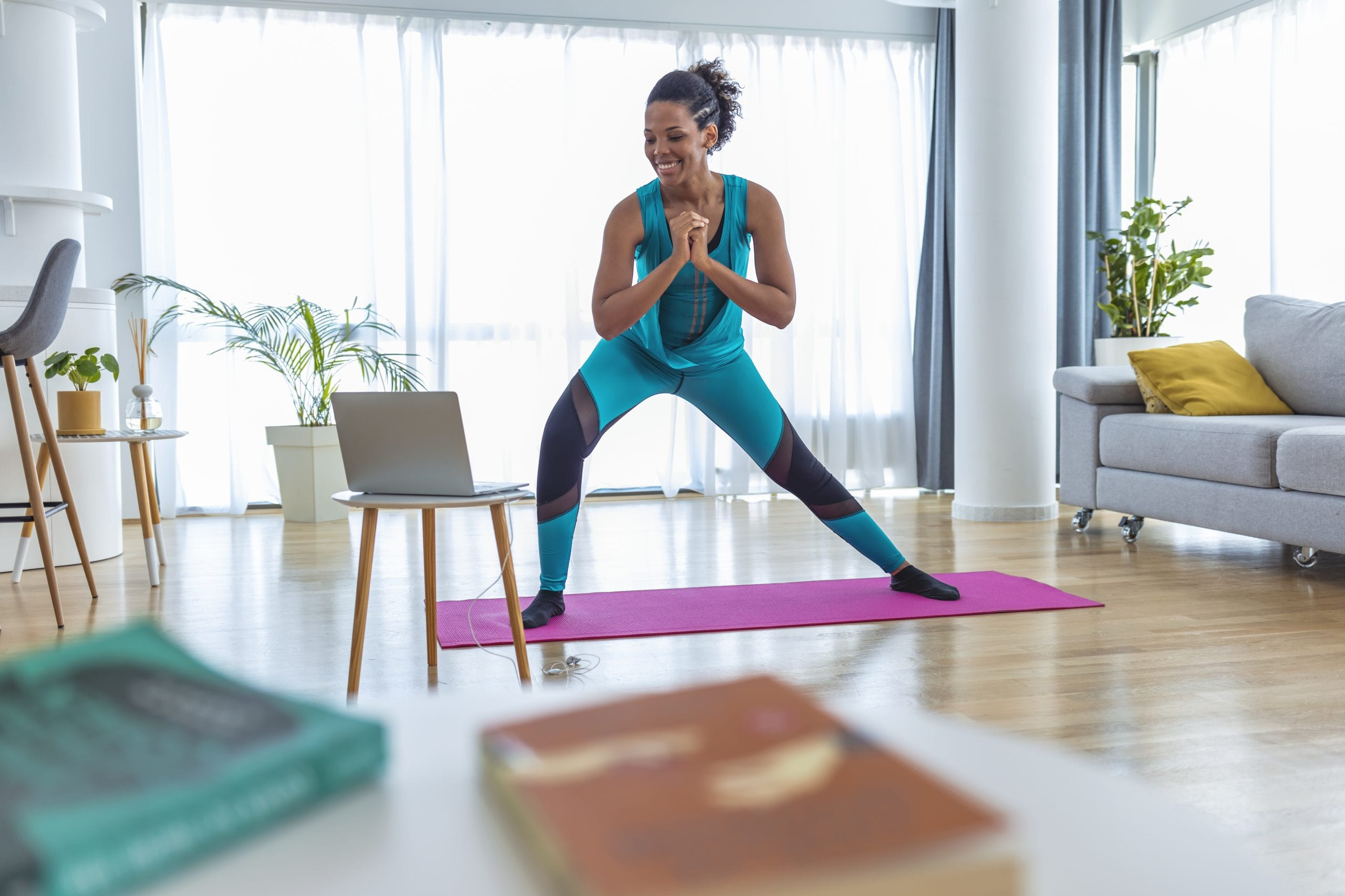 Beautiful African-American Woman Exercising Pilates, Yoga, Fitness at Home Looking at the Laptop.