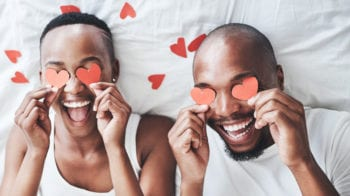Shot of a happy young couple playing with cut out red hearts in bed at home