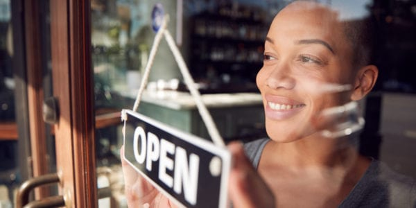 Black female business owner puts an open sign in the window