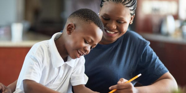 A Black mother and son sit at a desk doing schoolwork and smiling.