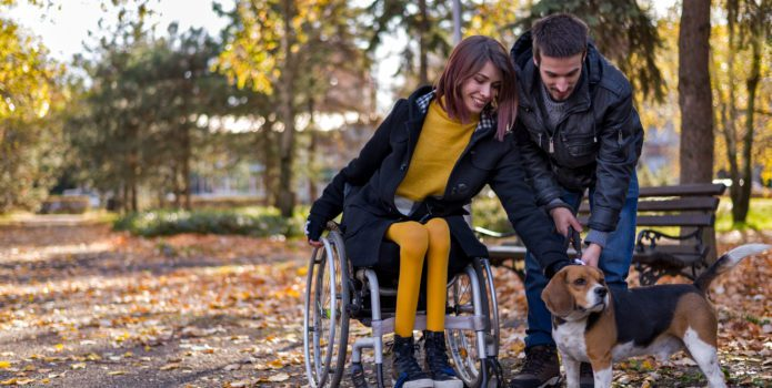 Disabled girl with boyfriend playing with dog in the park in autumn